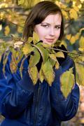 smiling girl amongst the autumn leaves - stock photo