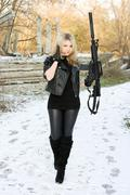 Sexy young woman with a gun - stock photo