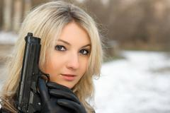 Sweet woman with a weapon Stock Photos