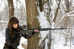 Beautiful woman with a sniper rifle - stock photo