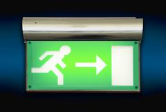 Emergency exit sign glowing green Stock Photos