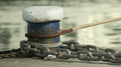 Mooring post with rope and chain wrapped around bollard Stock Footage