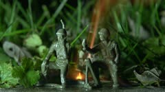 Two plastic army men burning in grass Stock Footage