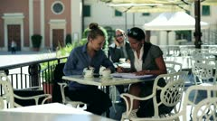 Two woman on businessmeeting sitting in cafe and talking together, outdoors Stock Footage