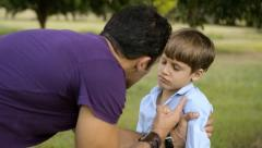 Parenthood and children education, angry man scolding boy in park Stock Footage