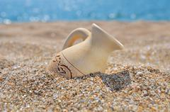 Ancient amphora on the beach sand Stock Photos