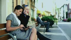 Businesswomen working sited on a bench at the city park - stock footage
