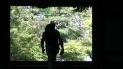Silhouette of a Western backpacker entering a Japanese temple, Asia - stock footage