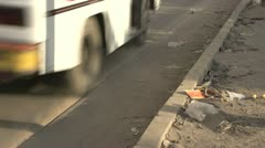 Dirty street detail, garbage strewn about, traffic through frame Stock Footage
