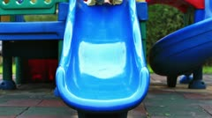 Cute little girl, outside in summer, playing on a slide. Stock Footage