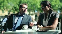 Businesspeople sitting at patio table ouside and talking Stock Footage