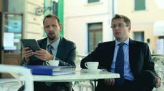 Businessmen sitting in the restaurant ouside with tablet computer and documents Stock Footage