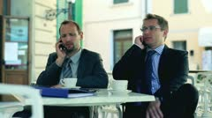 Businessmen sitting in the restaurant ouside and talking on cellphones Stock Footage
