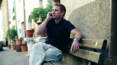 Handsome tourist sitting on bench and talking on cellphone - stock footage