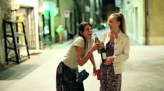 Drunk women with bottle of vine standing on the street in the evening Stock Footage