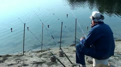Many fishing rods and angler smoking Stock Footage