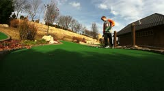 Boy playing miniature golf frustrated and picks up ball and puts in hole. Stock Footage
