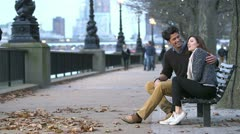 Couple enjoy a romantic moment, sitting on a London bench beside the river Stock Footage