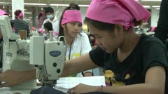 Asian Garment Industry Factory: MS garment worker and worker in background Stock Footage