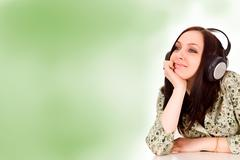 Woman with headphones in front of a green background Stock Photos