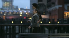 Couple stroll together by the side of the river Thames as night falls - stock footage