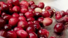 Cranberries falling into dish - stock footage