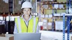 Woman in warehouse with laptop Stock Photos