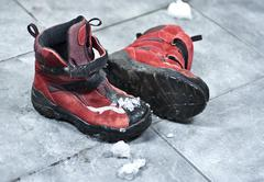 Winter shoes making a mess in the entrance Stock Photos