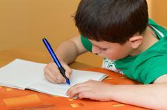 boy writting homework from school in workbook - stock photo