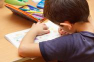 Boy doing homework  with color pencil, painting fruits Stock Photos
