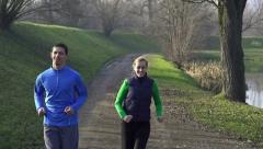 Stock Video Footage of Couple jogging in the park, crane shot, slow motion HD