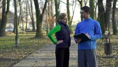 Female jogger with personal trainer in park, crane shot HD Stock Footage