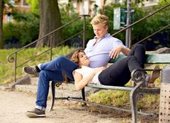 man looking at his girlfriend resting on his lap - stock photo