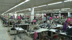Textile Garment Factory Workers: WS pan right to left on garment factory floor Stock Footage