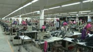 Stock Video Footage of Textile Garment Factory Workers: WS pan right to left on garment factory floor