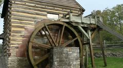 Water gently flowing in a stream turning an old mill wheel Stock Footage