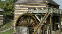Water gently flowing in a stream turning an old mill wheel - stock footage