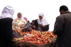 Veiled arab women buy apples in a street market .. Stock Photos