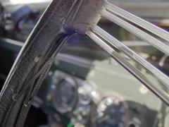 Retro steering wheel close up with out of focus gauges in a Land Rover Series II - stock photo