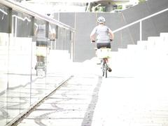 Cycling away from camera into white light past a glass barrier Stock Photos
