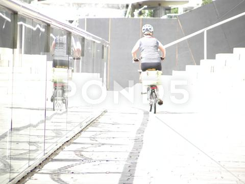 Stock photo of Cycling away from camera into white light past a glass barrier
