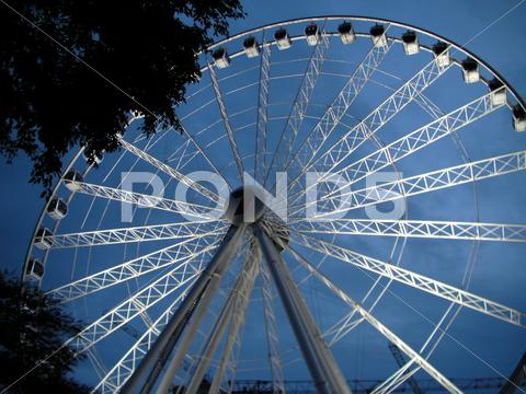 Stock photo of Big millennial tourist attraction wheel at dusk
