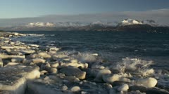 Icy Waves Splashing on Beach with Frozen Chunks Scenic Pan Stock Footage