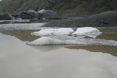 Glacier with black lava ice melting in lake Stock Photos