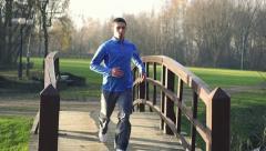 Man jogging in park, crane shot, slow motion HD - stock footage