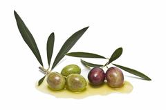 Olives with leaves in oil. Stock Photos