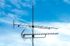 Old analog television antenna against blue sky Stock Photos