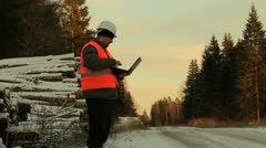 Lumberjack with the computer and cell phone near the log pile in the woods Stock Footage