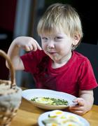 young boy eating spinach - stock photo