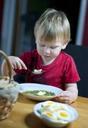young boy eating spinach soup with egg - stock photo